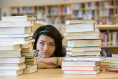 School girl (14-15) looking at stacks of books in library