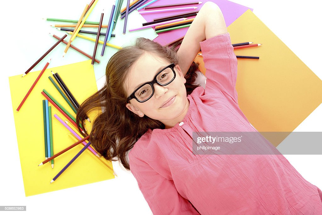 school girl lying on the floor with color pencils : Stock Photo