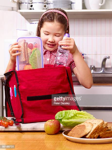 School girl packing lunchbox in school bag.