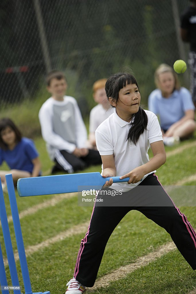 school girl playing cricket : Stock Photo