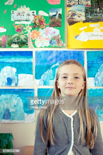 School girl (8-9) posing in classroom : Stock Photo