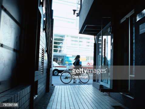 School girl pushing a bicycle : Stock Photo