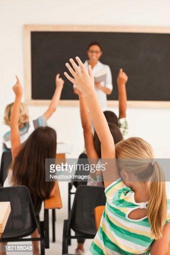 School girl raising her hands along with classmates