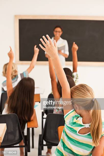 School girl raising her hands along with classmates