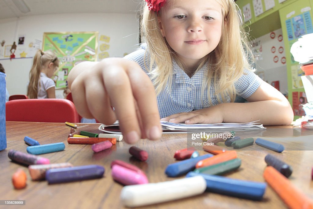 school girl reaching for coloured crayons : Stock Photo