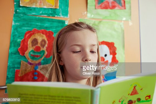 School girl (8-9) reading book : Bildbanksbilder