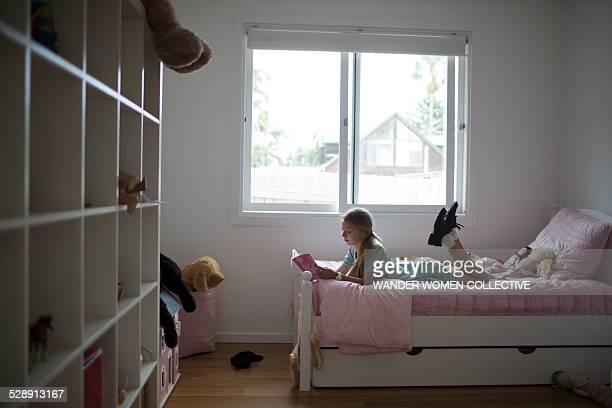 School girl reading in bedroom at home