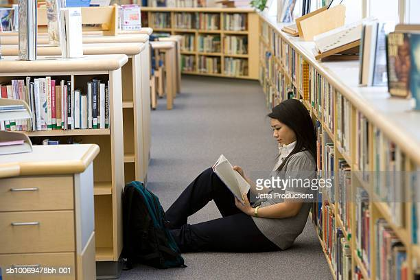 School girl (14-15) reading on floor by bookshelf in library