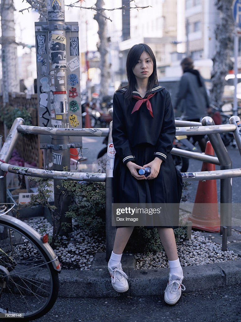 School girl sitting on a metal railing : Stock Photo