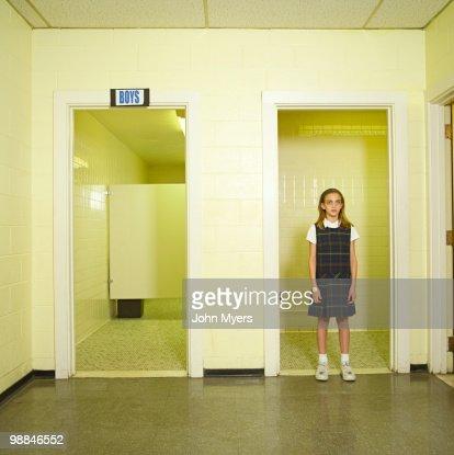 School girl standing in doorway of boys bathroom stock for Girls in bathroom with boys