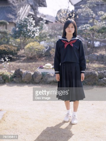 School girl standing in the front yard : Stock Photo