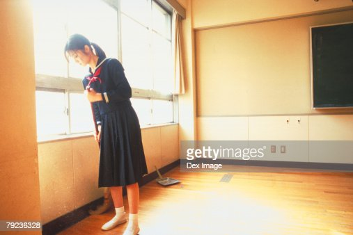 School girl sweeping the floor : Stock Photo