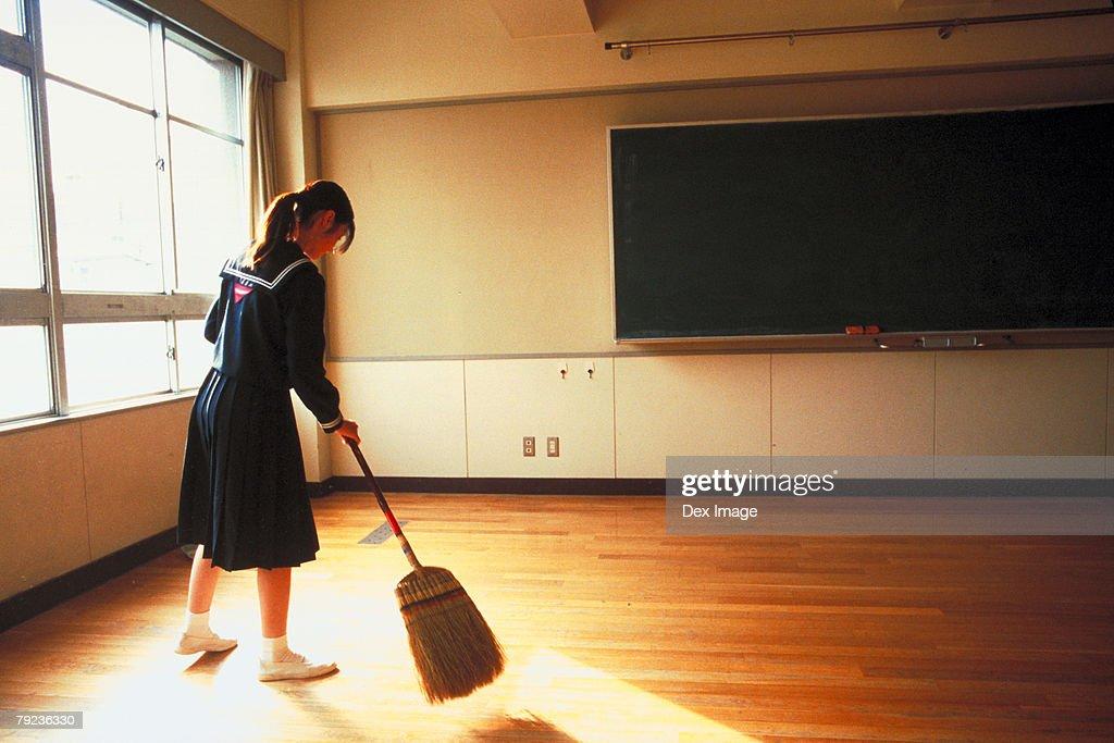 School girl sweeping the floor : Stock Photo