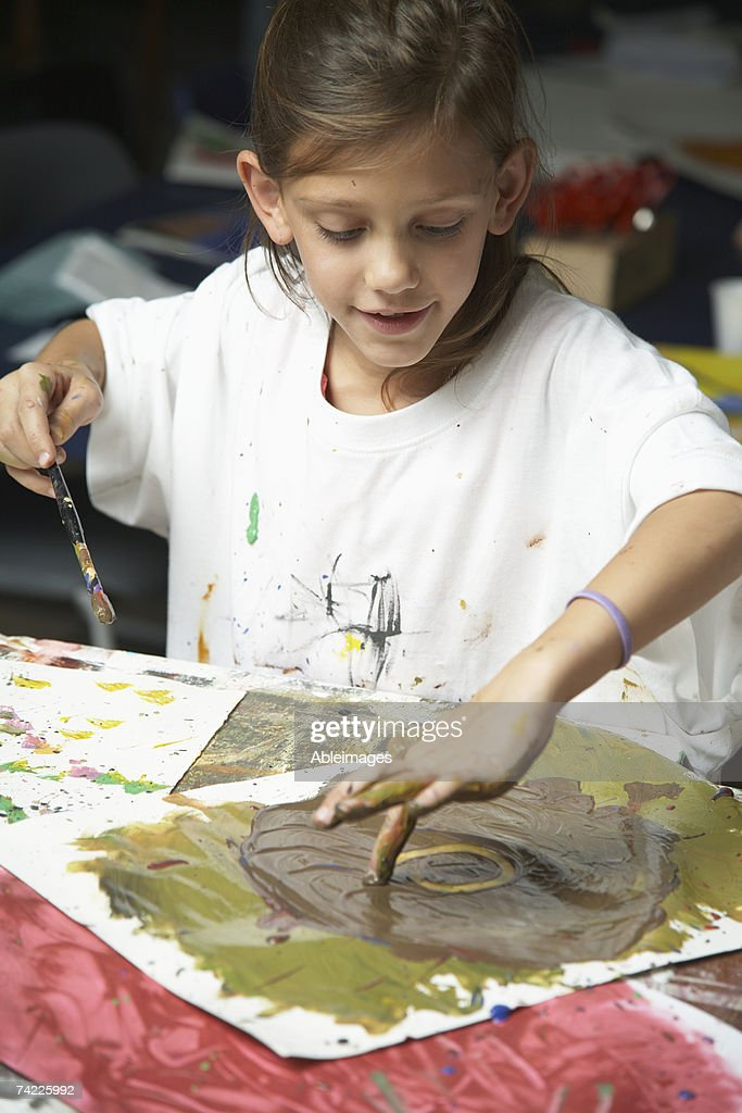 School girl (8-9) using hands and brush to paint onto paper : Stock Photo