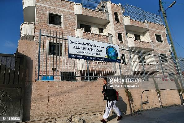 A school girl walks past the AlNkhba School a private Palestinian school in the Sur Baher district of Israeliannexed east Jerusalem on February 23...