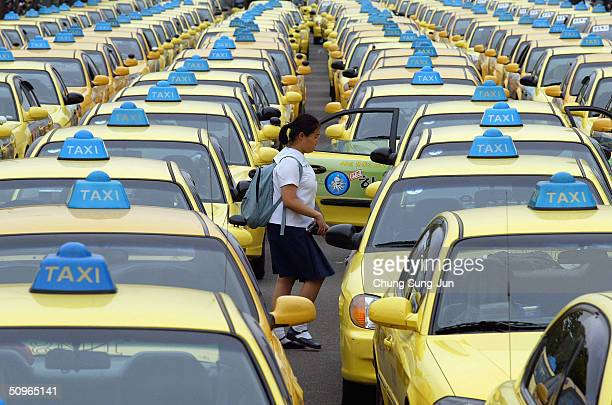A school girl walks through rows of taxis parked on a road on June 16 2004 in Seoul South Korea Taxi drivers and metal workers went on strike to...