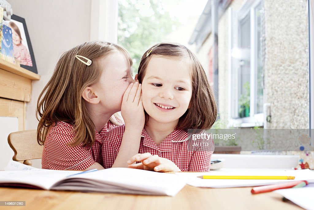 school girl whispering in girl's ear