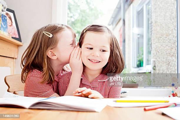 school girl whispering in girl's ear