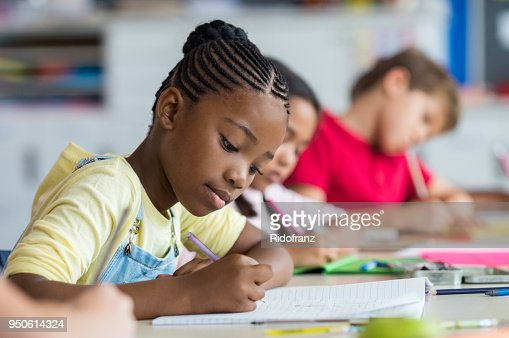 School girl writing in class : Foto de stock