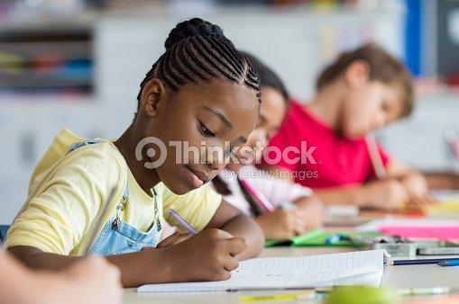 School girl writing in class : Stock Photo