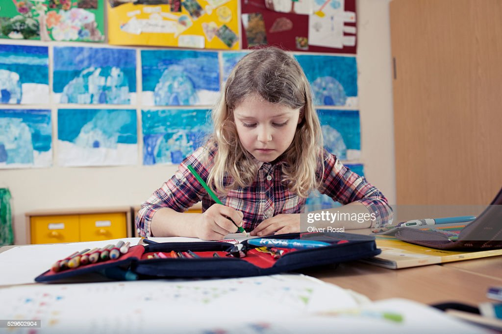 School girl (6-7) writing in classroom : Stock Photo