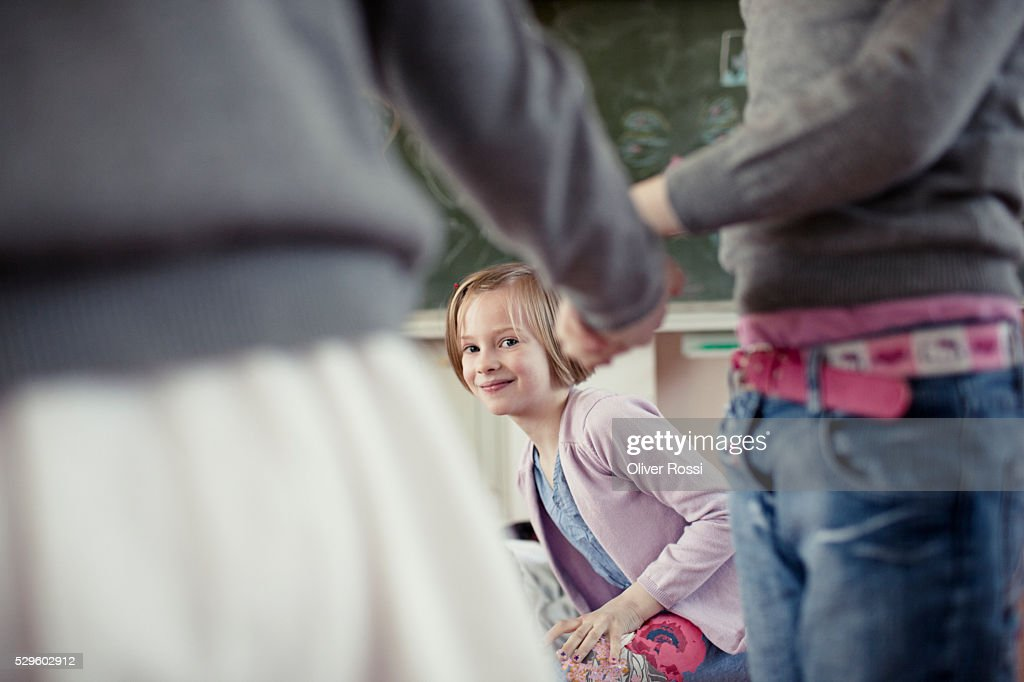 School girls( 6-7) and school boy (6-7) having fun in classroom : Foto de stock