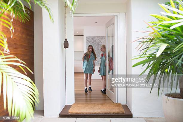School girls leaving home front door
