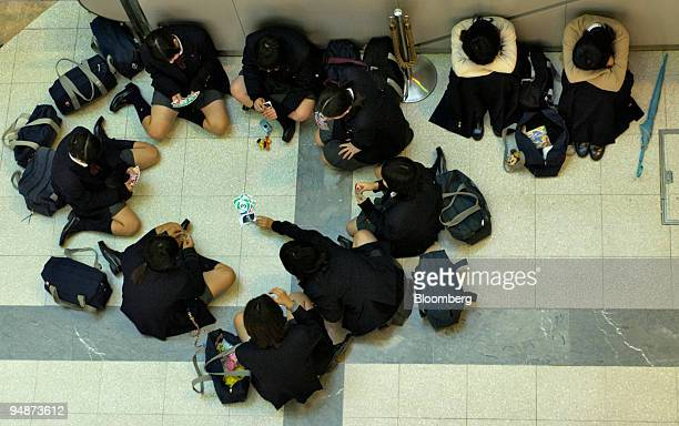 School girls play a card game and two women sleep on the floor at Tokyo's Haneda Airport on October 20 2004 Typhoon Tokage which reached Japan's...