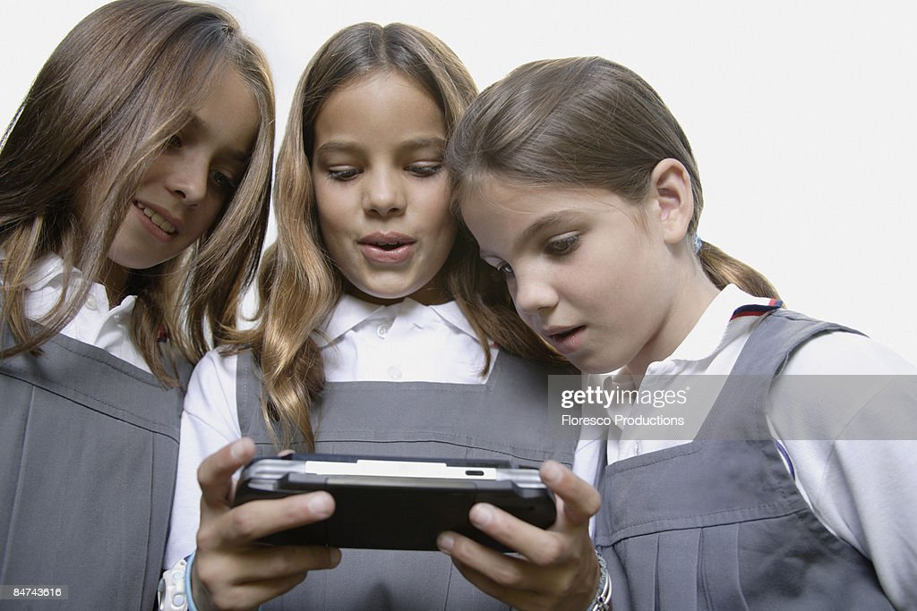 School girls playing handheld video game : Stock Photo