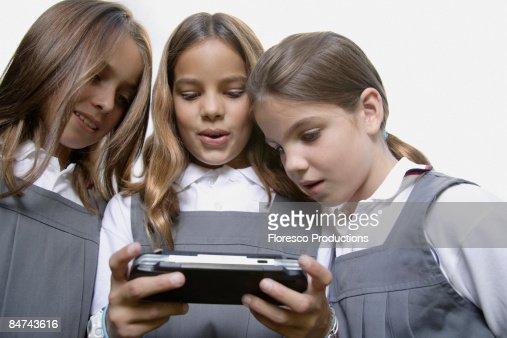 School girls playing handheld video game : Foto de stock
