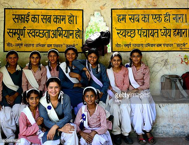School girls pose in front of wall with Sanitation quotes written on it to promote Swachh Bharat Abhiyan on February 23 2015 in New Delhi India