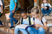 Two young girls sitting together on stairs and studying after school. Elementary schoolgirls studying the notes on copybook. Happy african girl and her friend doing homework on notebook at primary sch
