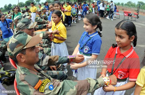 School girls ties 'Rakhi' on the wrist of army soldiers during the Raksha Bandhan festival celebrations at a school in Kathua about 85 KM on August 5...
