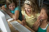 School girls (10-11) using computers in classroom