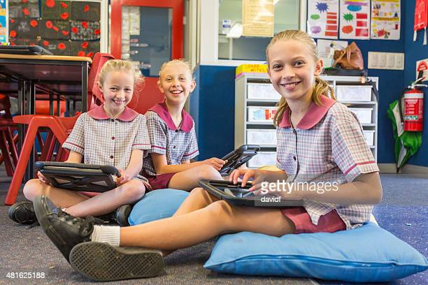 School Girls Using Tablet Computers for Online Learning in Classroom