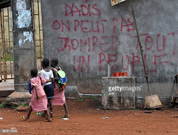 School girls walk on October 22 2009 near a building covered with graffito reading in French 'Dadis one cannot deceive a whole nation' in the Mototo...
