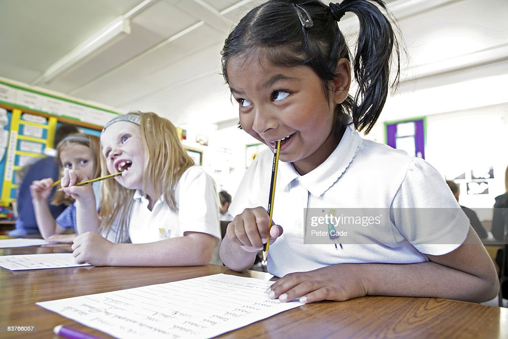 school girls writing in class : Stock Photo