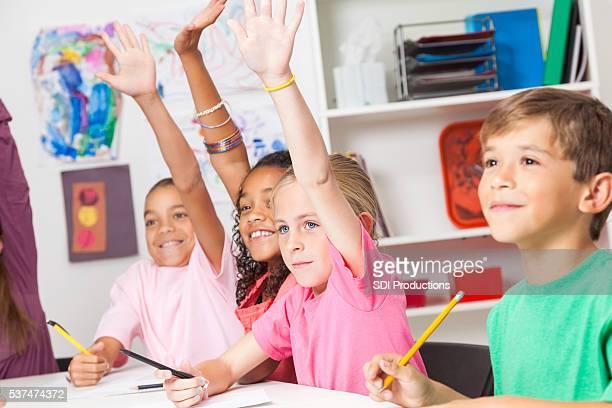 School kids answer questions in class