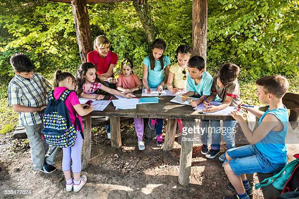 School kids coloring on a field trip with their teacher.