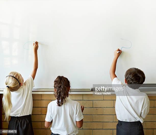 3 school kids drawing on whiteboard