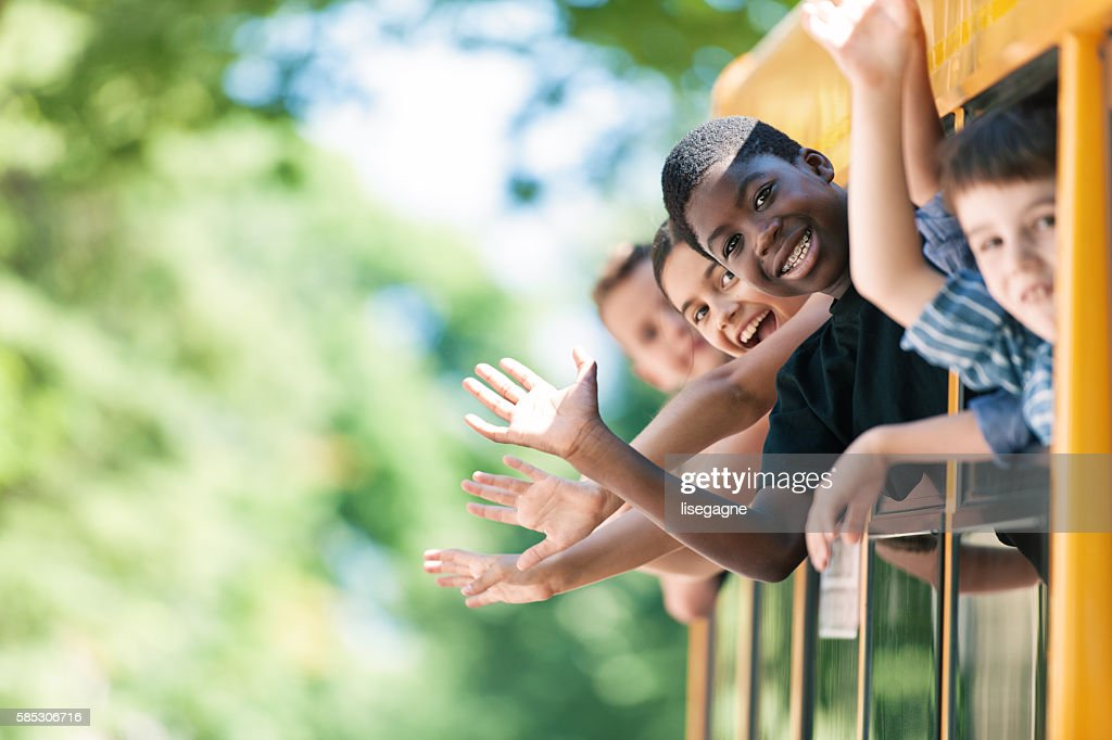 School kids hanging out bus windows : Stock Photo