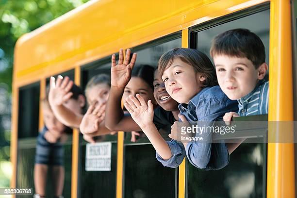 School kids hanging out bus windows