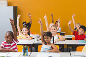 Smiling school kids raising hand in classroom at school