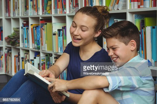 School kids reading books in library at school : Stock Photo