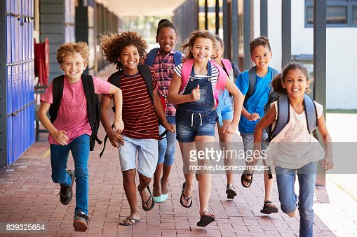 School kids running in elementary school hallway, front view : Stock Photo