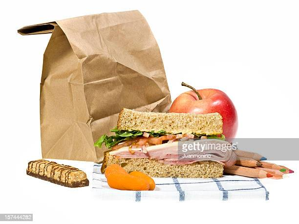School lunch next to brown paper bag on a white background