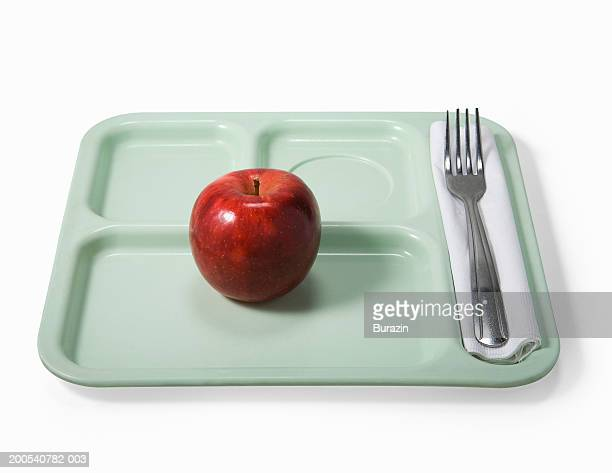 School lunch tray with apple, against white background, overhead view