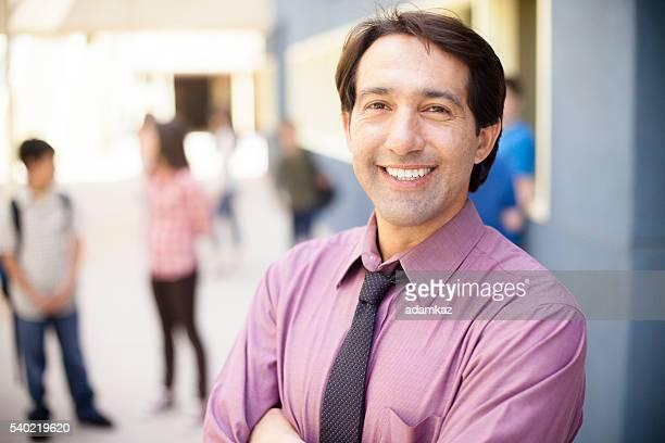 Preside sorridente di fronte a studenti nel città universitaria