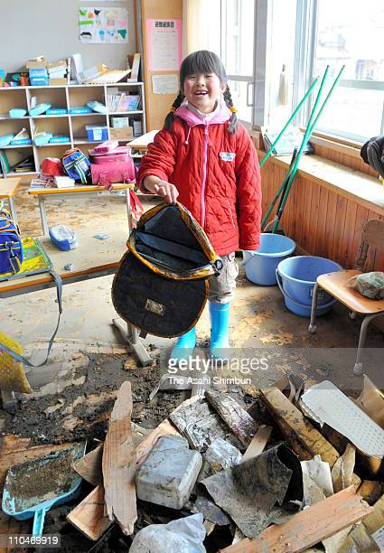 A school pupil smiles as she found her bag in the muddy school room at Ryori Elementary School on March 18 2011 in Ofunato Iwate Japan Thousands died...