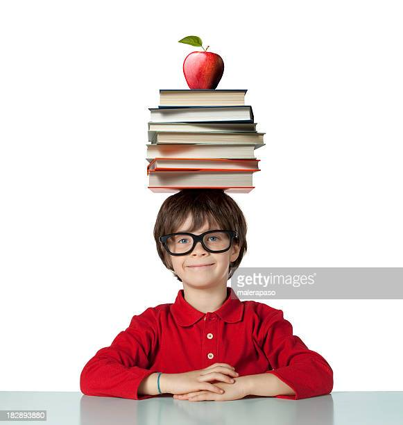 School pupil with pile of books on his head